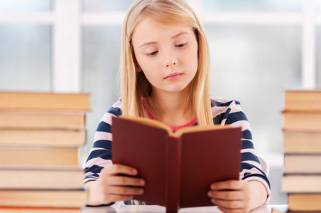 I love to study! Cheerful little girl leaning at the book stack while sitting at the table