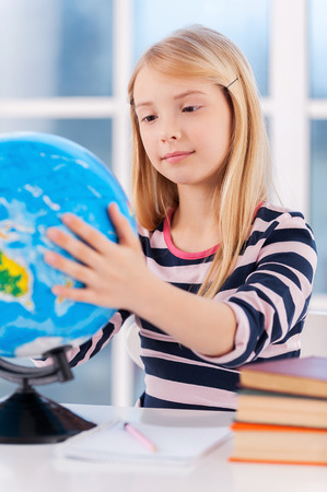 Examining globe. Cheerful little girl examining globe while sitting at the table photo