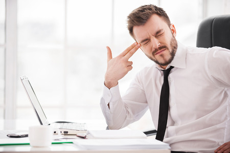 Depressed and frustrated. Depressed young man in formalwear touching his temple with finger gun and keeping eyes closed while sitting at his working place photo