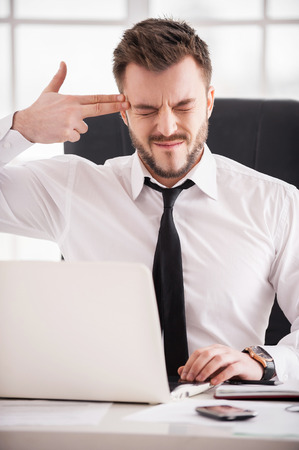 Monday morning suicide. Frustrated young man in formalwear touching his temple with finger gun and keeping eyes closed while sitting at his working place photo
