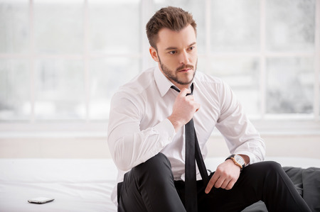 Tired executive. Young man in formalwear taking off his necktie while sitting on the bed   photo