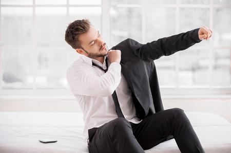 levantandose: Preparándose para un nuevo día de trabajo. Hombre joven barba vestirse la chaqueta mientras se está sentado en la cama Foto de archivo