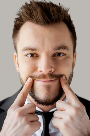 fake smile: Making a fake smile. Portrait of young man in formalwear making a smile by his fingers while standing against grey background Stock Photo