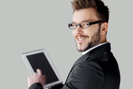 Confident in his tablet. Rear view of cheerful young man in formalwear and glasses working on digital tablet and looking over shoulder while standing against grey background photo