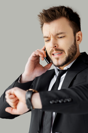 I will be in time! Portrait of worried young man in formalwear talking on the phone and checking the time while standing against grey background photo