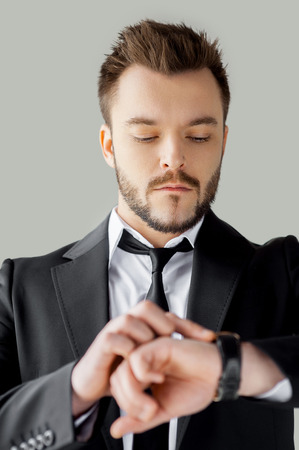Time management. Portrait of confident young man in formalwear checking the time while standing against grey background photo