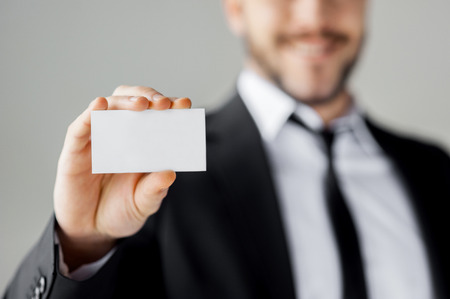 Copy space on his business card. Cheerful young man in formalwear showing his business card and smiling while standing against grey background photo