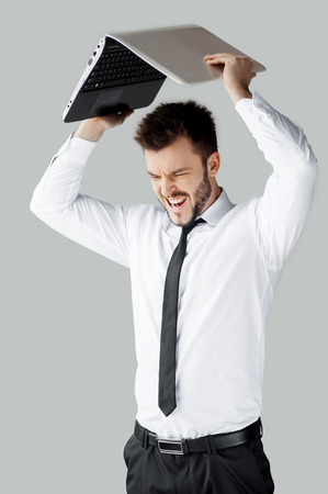 No more working! Furious young man in formalwear trying to break a laptop while standing against grey background