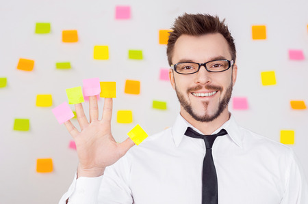 Creative business. Cheerful young man in formalwear holding adhesive notes on his fingers and smiling while standing against the wall with many adhesive notes on it  photo