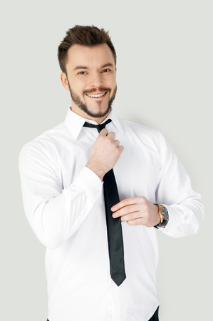 adjusting: Business dressing up. Handsome young man in formalwear adjusting his necktie and looking at camera while standing against grey background Stock Photo