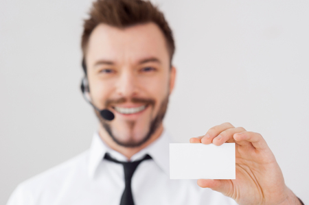 Just call this number! Handsome young man in formalwear and headset showing his business card and smiling while standing against grey background photo