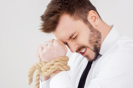 Tied up businessman. Side view of frustrated young businessman with tied up hands keeping eyes closed while standing against grey background photo
