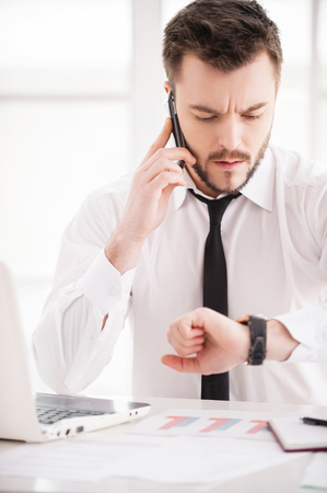 busy beard: Working moments. Handsome young beard man in shirt and tie working at his working place