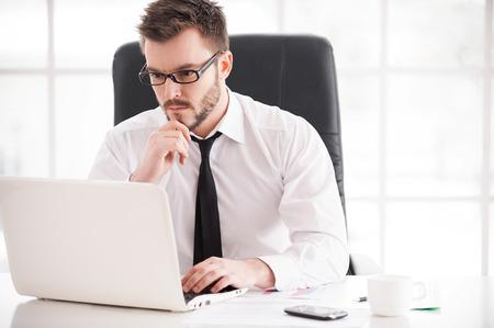 Geschäftsmann bei der Arbeit. Gut aussehender junger Mann Bart in Hemd und Krawatte, während der Arbeit am Laptop sitzt an seinem Arbeitsplatz Standard-Bild - 26313005