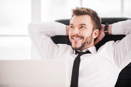 soñando: Sueño del día. Barba del hombre joven y guapo en camisa y corbata con las manos detrás de la cabeza y sonriendo mientras estaba sentado en su lugar de trabajo