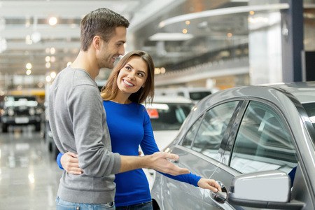 I like this car. Beautiful young couple standing at the dealership choosing the car to buy