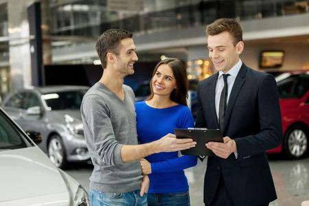 sales executive: This is good choice. Confident young salesman making deal with young couple