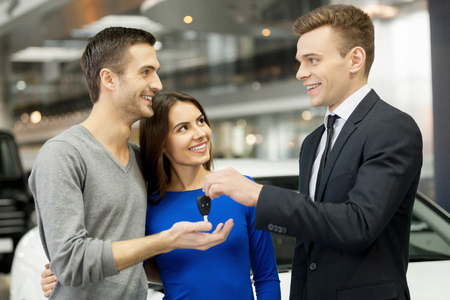 car sales: They have made a right vehicle choice. Young car salesman giving a key from the new car to the beautiful young owners