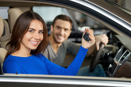 Proud of their brand new car. Beautiful young couple sitting inside of their new car at the dealership while woman showing keys photo