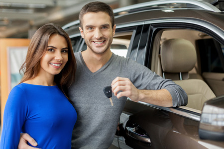 We have made the right choice. Handsome young men standing near the car at the dealership hugging his girlfriend and holding a key photo
