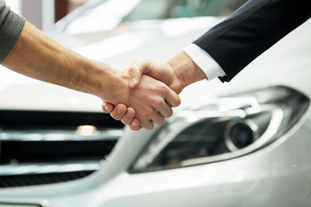 car showroom: Good deal. Close-up shot of the hands shaking in front of the car