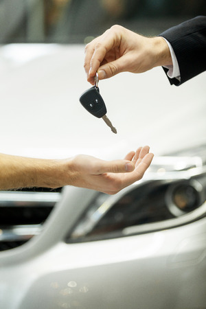 hand key: Drive carefully! Close-up shot of the car salesman hand giving a key to the owner Stock Photo
