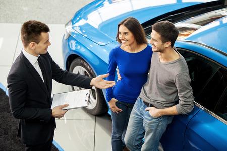 함께 처음으로 자동차를 구입. 고객에게 차의 기능에 대해 이야기 대리점에 서있는 젊은 자동차 세일즈맨의 높은 각도보기
