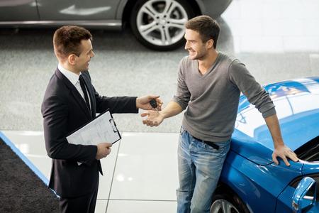 buen trato: Buen trato. Vista de �ngulo alto de vendedor de coches joven haciendo de acuerdo con el cliente en el concesionario