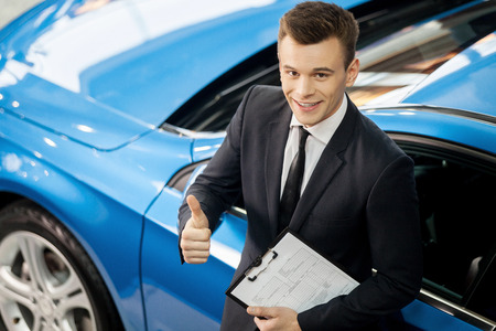 Let me assist you in your vehicle search. Top view of handsome young classic car salesman standing at the dealership holding a key photo