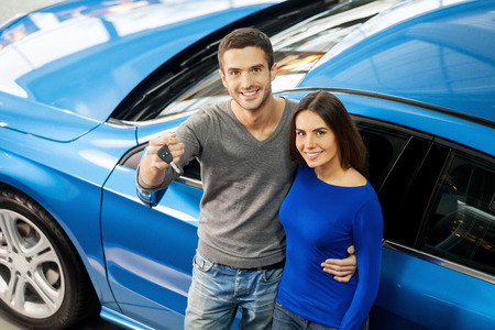We have made the right choice. Top view of young couple standing near the car at the dealership and holding a key photo