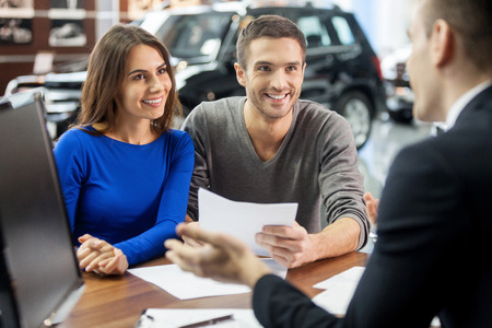 outstretching: This is good choice. Confident young salesman explaining all the car features to the young attractive owners Stock Photo