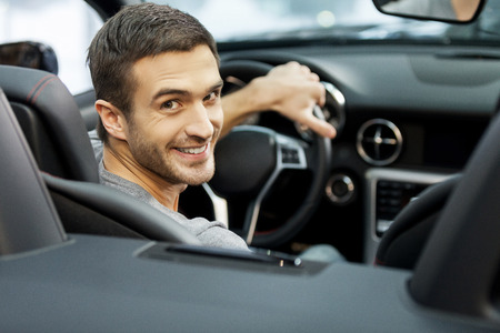 Happy cabriolet owner at the dealership. Handsome young men sitting at front seat of the car looking at camera photo