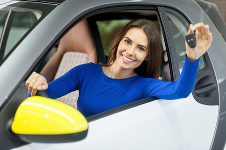 stetting: She has bought her dream car! Attractive young woman sitting at the front seat of the car and holding key Stock Photo