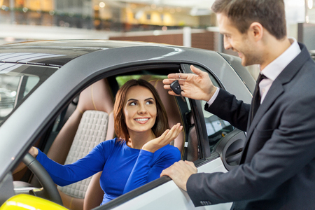 rental car: Ready for test drive. Handsome young car salesman giving key to young beautiful woman  Stock Photo