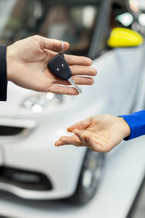 outstretching: She has made a right choice. Close-up shoot of the car salesman hand giving the key to female owner Stock Photo