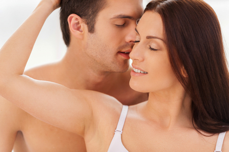 True passion. Handsome young shirtless man kissing his girlfriend photo