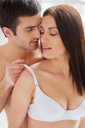 Taking off her bra. Handsome young shirtless man taking off a bra from his girlfriend photo