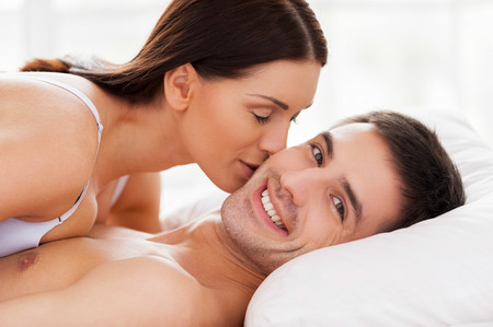 I love her! Beautiful young loving couple lying in bed while woman kissing her boyfriend at cheek  photo