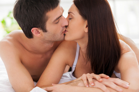 Loving couple kissing in bed. Beautiful young loving couple lying in bed and kissing photo