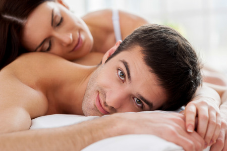 Loving couple in bed. Cheerful young loving couple lying in bed and smiling at camera photo
