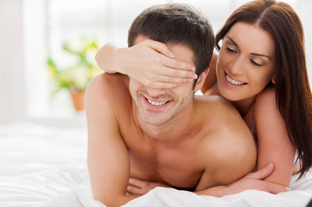 Playful loving couple. Cheerful young loving couple lying in bed while woman covering her boyfriend eyes photo