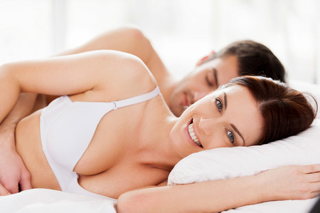 Loving couple in bed. Beautiful young loving couple lying in bed while woman looking at camera and smiling photo