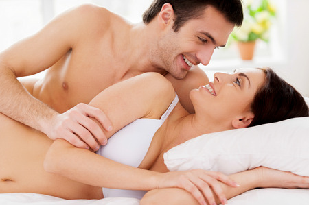 So good to wake up together! Beautiful young loving couple lying in bed and looking at each other with smile photo