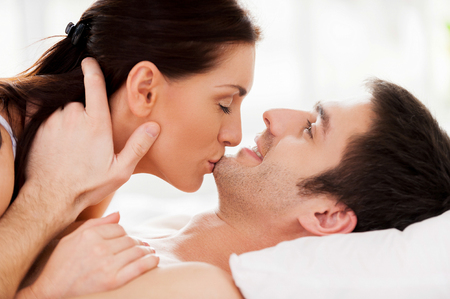 Sensual moments. Beautiful young loving couple lying in bed while woman kissing her boyfriend chin photo