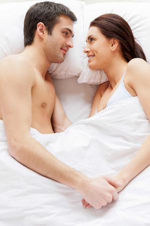 Loving couple in bed. Top view of beautiful young loving couple lying in bed and holding hands photo