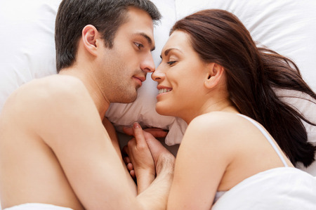 They love each other. Top view of beautiful young loving couple lying in bed and holding hands photo
