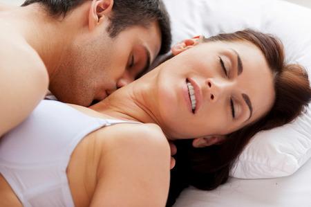 Lo amo a besarme! Pareja amorosa joven hermosa que tiene relaciones sexuales mientras está acostado en la cama
