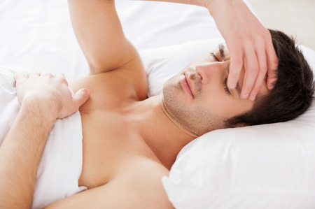 Insomnia. Handsome young shirtless man holding hand in hair and keeping eyes closed while lying in bed  photo