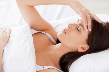 Insomnia. Attractive young woman holding hand in hair and keeping eyes closed while lying in bed  photo
