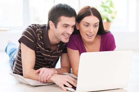 Spending their free time in the net. Beautiful young couple working on laptop together while lying on the floor at their apartment photo
